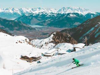 man in green skiing in resort